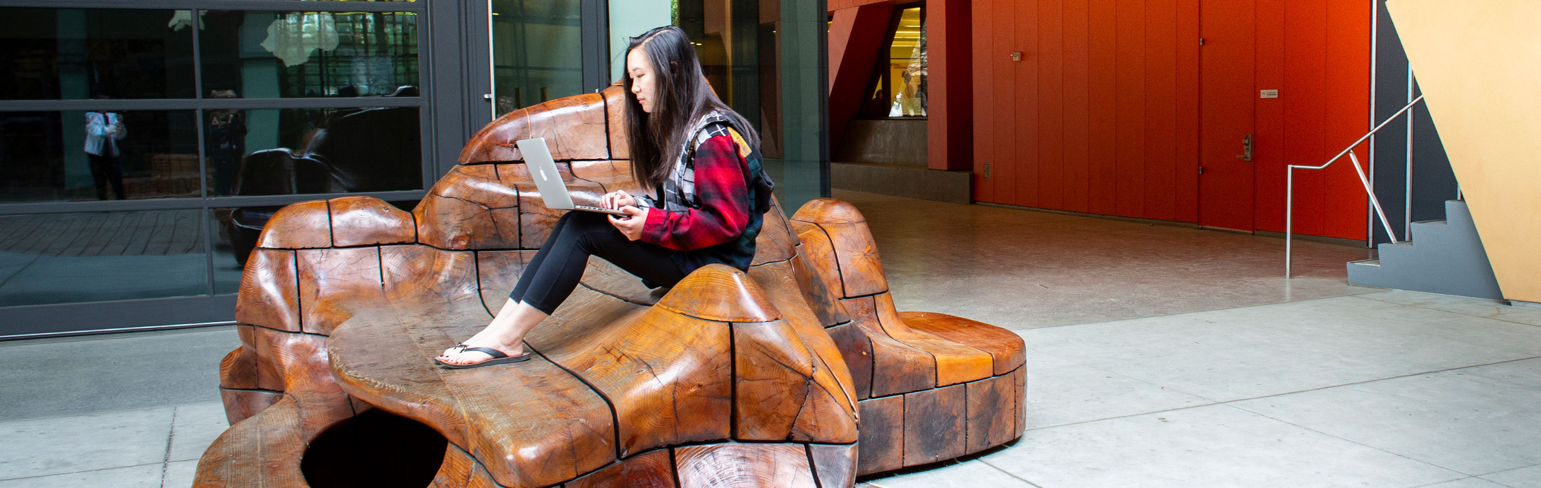 Student sitting on outside sculpture looking at her laptop computer