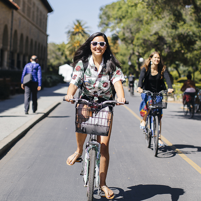 Women riding bikes on campus